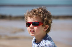 Child wearing sunglasses. With red beach scenery in the background out of focus royalty free stock photography