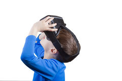 Child wearing virtual reality glasses watching movies or playing video games, isolated on white background. Royalty Free Stock Image