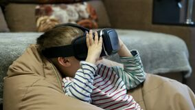 Child wearing virtual reality glasses and watching vr video at home at soft chair bag