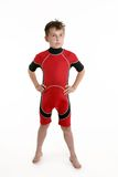 Child wearing a wetsuit. A young boy standing wearing a red and black wetsuit Stock Photography