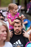 Child Wearing Wings Rides Father's Shoulders At Butterfly Festival Stock Photo