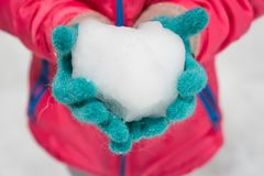 Child wearing winter gloves holding icy snow heart. In hands Royalty Free Stock Photos
