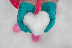 Child wearing winter gloves holding icy snow heart. In hands Royalty Free Stock Photography