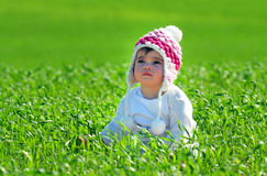 Child Wears Hat in Green Grass Stock Images