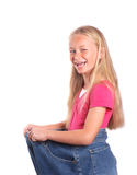 Child weight loss concept. Portrait of a cute little preteen Caucasian blond girl child with happy laughing facial expression wearing too big blue jeans. Image stock image