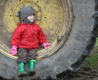 Child on wheel. Child in red siting on wheel Royalty Free Stock Photos