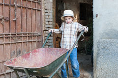 Child with wheelbarrow. Baby is coming out of the stable with a wheelbarrow Royalty Free Stock Photos