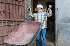 Child with a wheelbarrow. Child is coming out of the barn with a wheelbarrow Stock Images