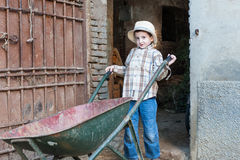 Child with a wheelbarrow. Child is coming out of the barn with a wheelbarrow Royalty Free Stock Photo