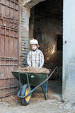 Child with a wheelbarrow. Child that loads the straw on the wheelbarrow Royalty Free Stock Image