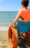 Child in a wheelchair looks at the sea. Child in wheelchair looks at the sea hopefully royalty free stock images