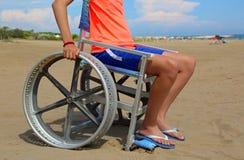 Child on the wheelchair on the sandy beach. In summer stock photos