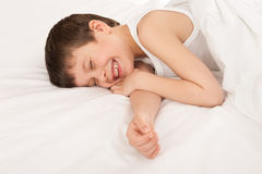 Child in white bed Royalty Free Stock Images