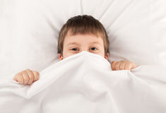 Child in white bed Royalty Free Stock Photos