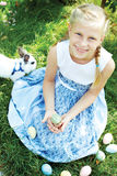 Child with white bunny searching for colorful eggs on meadow. royalty free stock images