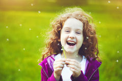 Child with white dandelion in your hand. Background toning instagram filter. royalty free stock image