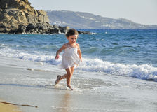 Child in a white dress running through the waves Stock Photos