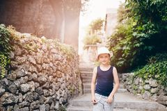 Child in white hat walking on narrow street of old town Royalty Free Stock Photo