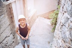 Child in white hat walking on narrow street of old town Stock Images