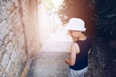 Child in white hat walking on narrow street of old town Royalty Free Stock Photos