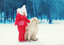 Child with white Samoyed dog in park winter Stock Photos