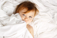 Child White Sheet Cover Lay. Beautiful child wrapped in white sheets Royalty Free Stock Photos