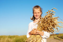 Child in white shirt holding wheat ears in the hands Stock Photography