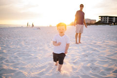 Child in White Shirt Running on White Sand during Dawn Near Man in Black Shirt Royalty Free Stock Image