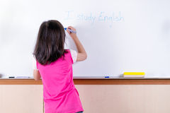 Child at whiteboard. Writing I study English Stock Image