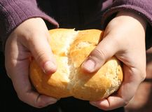 Child who breaks a piece of bread with  hands Stock Image