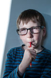 Child who pondered. Child with glasses and pencil who pondered Stock Photo