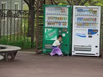 Vending child in front of vending machine royalty free stock photo