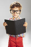 Child who wears plaid shirt with a book in hands Stock Photography