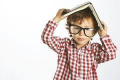 Child who wears plaid shirt with a book on his head Stock Photos