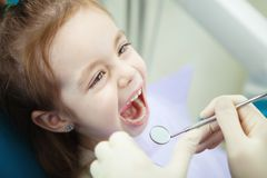Child with wide open mouth at dentist office. Lies on chair and waits for checkup. Doctors hands in sterile rubber gloves that hold instrument with magnifying stock photography