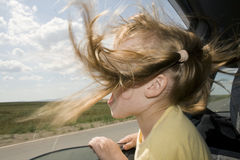Child will go in the Car. Little fun girl speeds in car near the open window Royalty Free Stock Photos