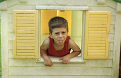 Child in Window. Photo of a Child in Playhouse Sticking Out Tongue Stock Photography