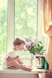 The child at a window Stock Image