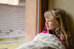 Child by the window. Beautiful blond girl looking through window Royalty Free Stock Image