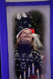 Child by window at Christmas. Young boy in Santa hat looking out of frosty window of house at Christmas with candles in foreground Royalty Free Stock Photo