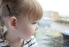 Child at the window. Close up of a preschool girl looking out of a rain covered window Stock Photo