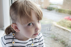 Child at the window. Preschool girl sitting at a window on a rainy day, and looking directly at the camera Royalty Free Stock Photos