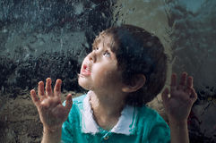 Child and window on a wet rainy day Royalty Free Stock Images