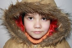 Child in winter. Little boy ready to go out with his new winter jacket....open big eyes, to see all things around Royalty Free Stock Image