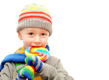 Child in winter clothes. A young boy in winter clothes eating a colorful lollypop Royalty Free Stock Photography