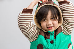 Child in Winter Coat. Cute Asian girl shivering in coat, studio isolated white background Royalty Free Stock Photo