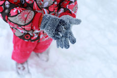 Child in winter gloves. Girl, child, gloves, winter, snow, snowflakes, cold, red, removes Royalty Free Stock Photo