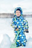 A child in winter with a green shovel goes on a snow-covered road stock photo
