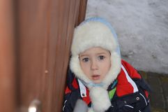 A child in a winter hat with a frightened look stock photo