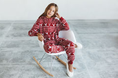 Child in winter pajamas. 10 years old child dressed in warm Christmas pajamas sitting on modern rocking chair in concrete scandinavian interior. Lazy winter royalty free stock images